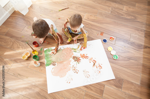 Two Brothers Paint With Gouache On A Large Sheet Of Paper