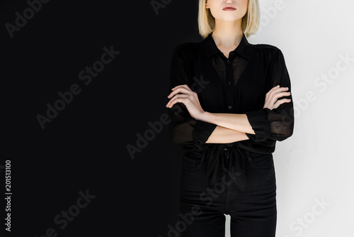 Fototapeta  cropped image of stylish blonde woman in black clothes standing with crossed arm