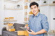 Startup small business entrepreneur SME, asian man writing on clipboard. Portrait young small business owner at warehouse office, online marketing packing delivery, SME e-commerce moving house concept