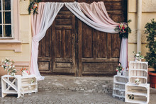 Rustic Wedding Photo Zone. Wooden Barn Doors With Fabric And White Boxes With Flowers And Candles At Stylish Wedding Photo Booth. Shabby Chic. Luxury Arrangements