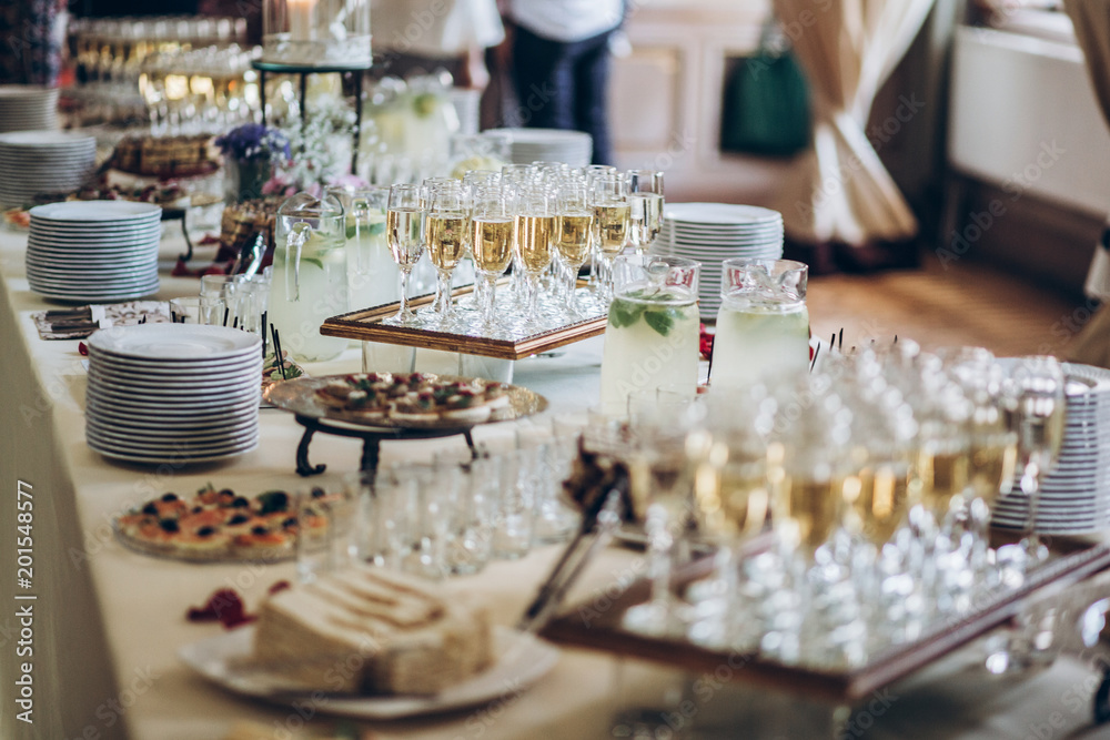 Fototapeta stylish champagne glasses and food  appetizers on table at wedding reception. luxury catering at celebrations. serving food and drinks at events concept