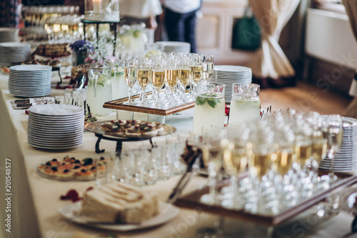 Cuadros en Lienzo stylish champagne glasses and food  appetizers on table at wedding reception