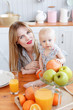 happy young family have lunch time with fresh fruits and vegetable food in bright kitchen. Funny girl with mom on kitchen.