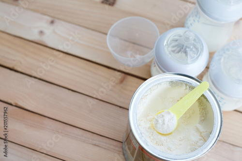 Milk powder for baby in measuring spoon in can and milk bottle on wooden table with copy space.