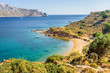 Beautiful sunny coast view to the greek blue sea with crystal clear water beach with some boats fishing cruising surrounded by hills, Kokkina Beach, Leros, Dodecanese Islands/ Greece – July 18 2017