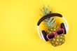 Leinwandbild Motiv Hipster pineapple with sunglasses and headphones. Top view against a yellow background. Minimal summer concept.