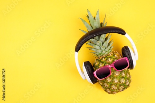 Hipster pineapple with sunglasses and headphones. Top view against a yellow background. Minimal summer concept.