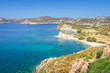 Amazing sunny coast view to a empty holiday bay Didymes beach with crystal clear blue water sandy beach for sunbathing and some boats cruising fishing in background, Patmos Island, Dodecanese, Greece