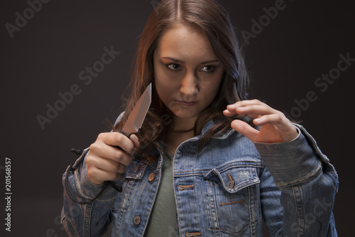 Teen girl with a knife in hand, ready to defend herself against an attacker Wallpaper Mural