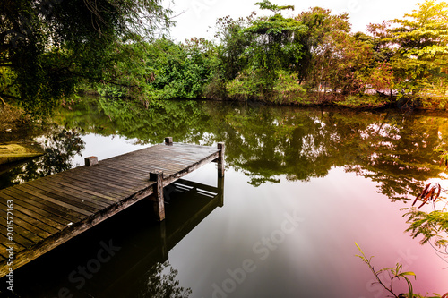 Photographie  Long exposure of pier in calm lake, with nature all around, water is silky smoot