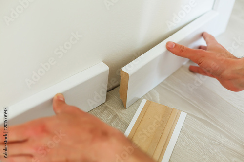 Mans hands putting white baseboard, do it yourself Wallpaper Mural