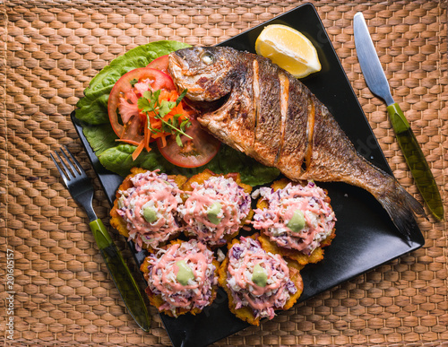 fried fish with fried plantain and salad, beach food in Venezuela