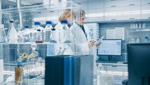 Female And Male Senior Scientists Walking Through Busy Modern Laboratory. They Have  Discussion About Documents.