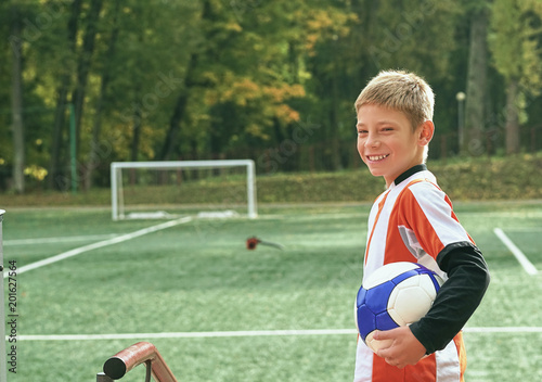Smiling teenage boy with a soccer ball in his hand and soccer boots on the shoulder against the background of the stadium. Sports training in the field.