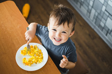 A Child In A T-shirt In The Kitchen Eating An Omelet, A Fork