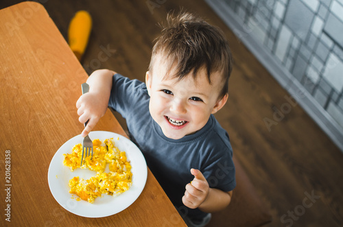 Spoed Foto op Canvas Kruidenierswinkel a child in a t-shirt in the kitchen eating an omelet, a fork