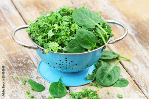 Shredded raw kale and spinach baby leaves in blue colander on rustic wooden surface with copy space