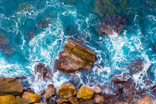Top Aerial View Of Blue Waves Crashing On Rocky Australian Coastline. Summer Seascape With Ocean Waves And Cliffs. Travel Concept Background