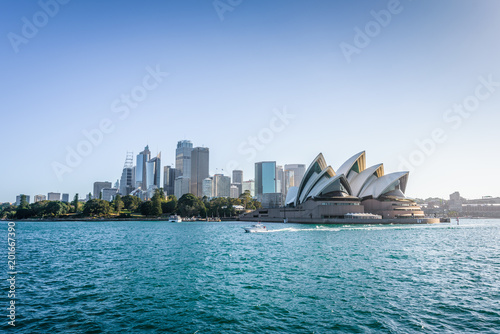 Wall Murals Sydney Beautiful sunny coast view to the Skyline and famous Opera House on bright warm day, cruising by ferry from harbour quay bridge to Manly City, Opera House and Quay,Sydney, NSW/ Australia – 10 12 2017