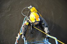 An Industrial Diver With Scuba Diving And In A Protective Suit Climbs Out Of The Water Along The Stairs.