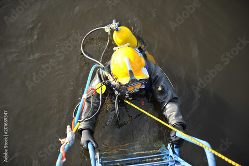 Photo  An industrial diver with scuba diving and in a protective suit climbs out of the water along the stairs