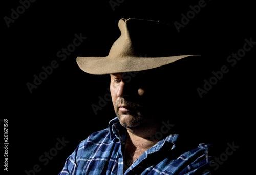 Cuadros en Lienzo A worker with downcast eyes on black.