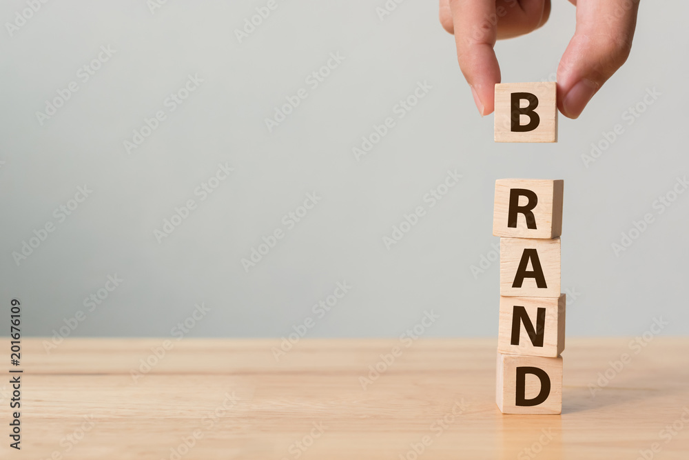 "Fototapeta Hand of male putting wood cube block with word ""BRAND"" on wooden table. Brand building for success concept"