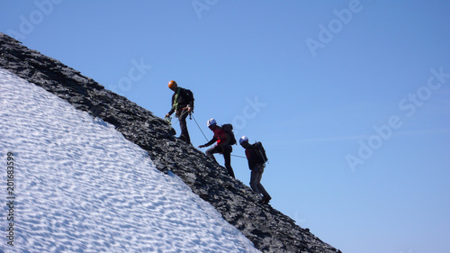 Photo  mountain guide and two clients heading to a high mountain peak and reaching the
