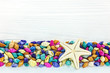 starfish with multicolored seashells border on white wooden boards. sea vacation background