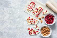 Cardamom White Chocolate Pomegranate Nuts Bark On Concrete Background. Top View, Space For Text.