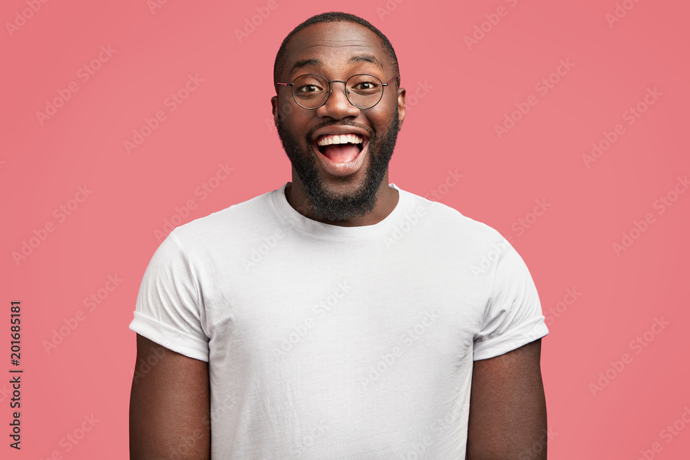 Fototapeta Waist up portrait of glad dark skinned handsome male model with happy expression, wears round spectacles, being in good mood as recieve bonus for diligent work, isolated over pink background