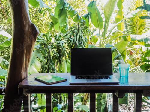 Fotografia laptop of a digital nomad on a wooden table in nature with a green tropical back