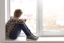 Lonely Little Boy Near Window Indoors. Child Autism