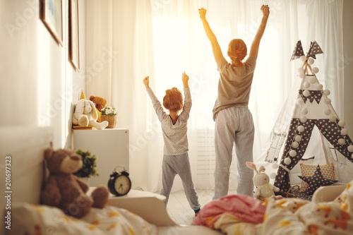 Obraz mother and child daughter stretch themselves after waking up in the morning