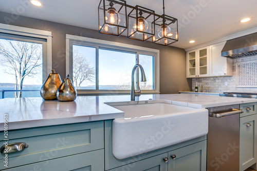 Beautiful kitchen room with green island and farm sink. Fototapet
