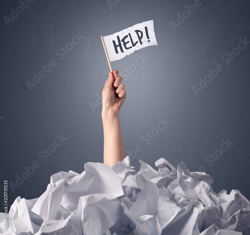 Photo Female hand emerging from crumpled paper pile holding a white flag with help wri