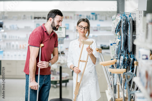 Man choosing crutches in the pharmacy Canvas Print