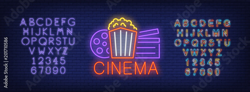 Cinema and alphabet neon sign set. Popcorn box, film reel, clapper board, violet colorful letters and numbers. Night bright advertisements. Vector illustrations in neon style for online movie