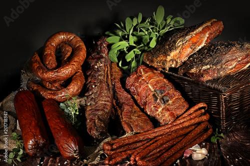 Fototapeta Wędzone wędliny, tradycyjny smak. Tradycyjnie wędzone wędliny w kompozycji na lnianym obrusie z ziołami obraz