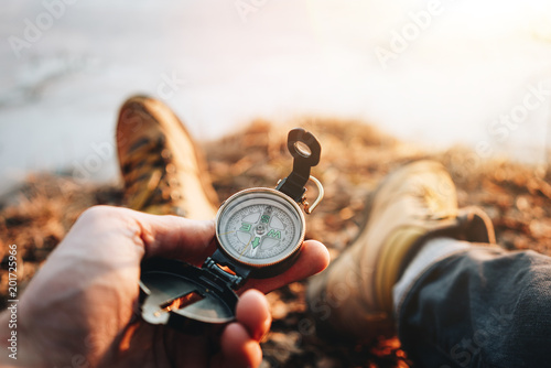 Fotografie, Obraz  Hipster traveler sitting and hold in hand compass