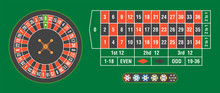 Casino Roulette Wheel With Casino Chips On Green Table