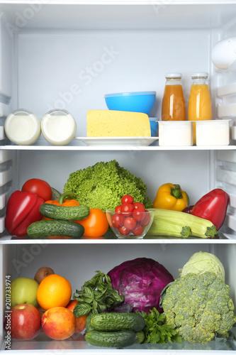 Open fridge full of vegetables and fruits