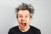 Unshorn And Unshaven Young Guy With Piercings On His Face Opening His Mouth And Screaming On Gray Background.