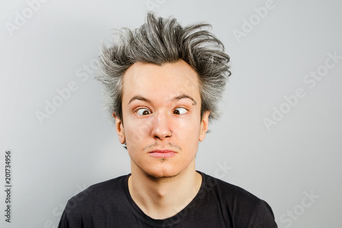 Fotografie, Obraz Unshorn and unshaven squint young guy with piercings on his face on gray background