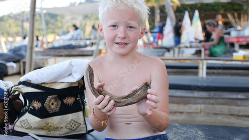 Fotografie, Obraz  A blond boy is sitting in a cafe on the beach, playing with a stick and peeling coconut, fanatizes