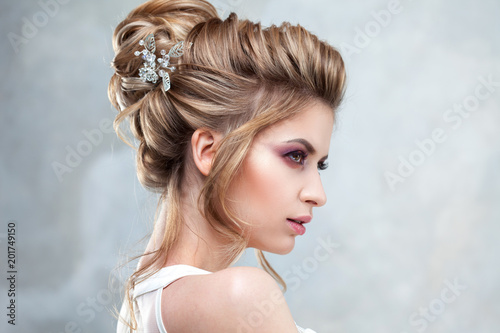 Photo sur Toile Salon de coiffure Young beautiful bride with an elegant high hairdo. Wedding hairstyle with the accessory in her hair