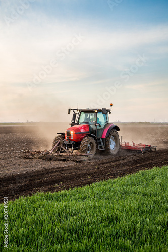 Tractor cultivating field at spring Wall mural