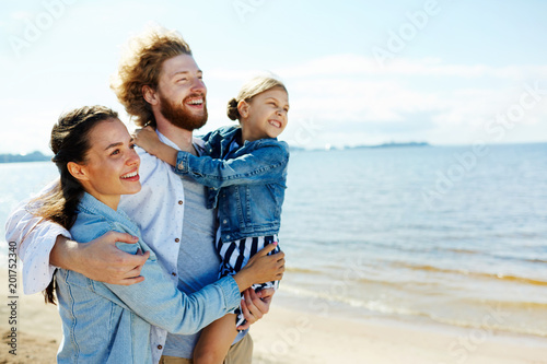 Fototapeta Happy family of three embracing while enjoying hot summer day on the beach at leisure obraz