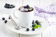 Chocolate Cake In A Mug With Blueberry And Powdered Sugar
