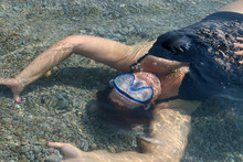 Woman Is Lying Supine Underwater On Pebble Of Sea Shallow.